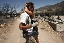 Leah Hogsten  |  The Salt Lake Tribune Amy Beattie hugs her father, Bruce Beattie, in front of the charred remains of his home Friday, June 29, 2012 in New Harmony.