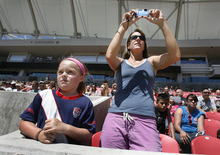 Scott Sommerdorf  |  The Salt Lake Tribune              Jane Benedict takes photos of the U.S. Women's national soccer team as her daughter Zoe watches the U.S. team hold its final practice Friday, June 29, 2012 in advance of its Olympic send-off match against Canada at Rio Tinto Stadium on Saturday. The practice session was open to the public.