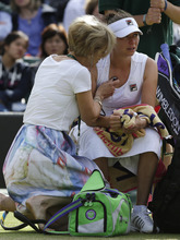 Vera Zvonareva of Russia, right, is examined by a doctor during a third round women's singles match against Kim Clijsters of Belgium  at the All England Lawn Tennis Championships at Wimbledon, England, Friday, June 29, 2012. (AP Photo/Anja Niedringhaus)