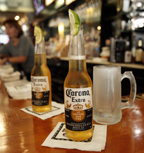 FILE - This Oct. 5, 2011 file photo, shows Corona Extra beers, sporting lime wedges, on the bar at Rick's Cafe in Chagrin Falls, Ohio. Anheuser-Busch InBev SA agreed Friday, June 29, 2012, to buy the half of Corona maker Grupo Modelo it doesn't already own for $20.1 billion in cash, in a deal that will greatly increase the size and dominance of the world's largest brewer. (AP Photo/Amy Sancetta, File)