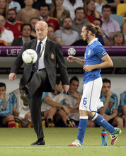 Spain head coach Vicente del Bosque, left, kicks the ball as Italy's Federico Balzaretti tries to take a throw-in during the Euro 2012 soccer championship final  between Spain and Italy in Kiev, Ukraine, Sunday, July 1, 2012. (AP Photo/Ivan Sekretarev)
