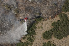 Leah Hogsten  |  The Salt Lake Tribune A helicopter tries to drown out the fire line on the mountain behind Lambert Park. A wildfire that started about 2 p.m. Tuesday in Lambert Park in Alpine has burned at least one structure -- a barn -- and 80 homes have been evacuated, according to the Lone Peak Police Department. Utah County Sheriff's Sgt. Spencer Cannon said the fire was human-caused, somehow sparked by a man working on a trackhoe near the Alpine rodeo grounds. Tuesday, July 3, 2012 in Alpine
