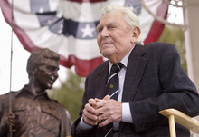 FILE - This Oct. 28, 2003 file photo shows actor Andy Griffith sitting in front of a bronze statue of Andy and Opie from the