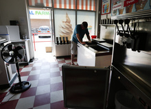 Tom Morgan cleans an empty ice cream freezer in his store in Towson, Md., Tuesday, July 3, 2012, as he waits for power to return for the first time since last weekend's severe storms. (AP Photo/Patrick Semansky)