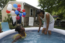 Curyl Green, right, and her daughter Ania, 11, keep cool in a pool in the aftermath of a storm that left their home without power, Tuesday, July 3, 2012, in Salem, N.J. More then a million customers from North Carolina to New Jersey and as far west as Illinois were without power Monday morning after a round of summer storms. (AP Photo/Matt Rourke)