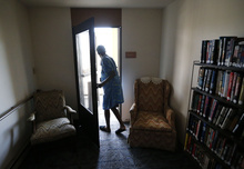 Janet Arnett looks out on a balcony in a common hall outside of her apartment in Epiphany House, a low-income senior home in Baltimore, Tuesday, July 3, 2012, as she awaits return of electricity for the first time since last weekend's severe storms. Utility crews struggled Tuesday to restore power to more than 1 million people in the eastern U.S. as frustration grew four days after storms that have led to 24 deaths so far. Officials worried the toll could rise because of stifling conditions and generator fumes. (AP Photo/Patrick Semansky)