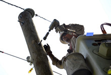 Gulf Power lineman Tommy Williams, of Pensacola, Fla., installs a bolt on a power line pole as his crew repairs downed power lines in Middleburg, Va., Tuesday, July 3, 2012. Severe storms swept through the area leaving many homes and businesses without electricity. (AP Photo/Cliff Owen)