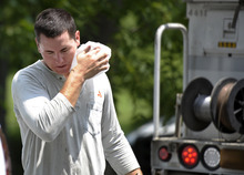 Gulf Power lineman Aaron Mott, of Pensacola, Fla., wipes sweat from his face with a wet paper towel after installing a new power line in Middleburg, Va., Tuesday, July 3, 2012. severe storms swept through the area leaving many homes and businesses without electricity. (AP Photo/Cliff Owen)