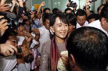 Myanmar opposition leader Aung San Suu Kyi, center, is welcomed by supporters upon her arrival at Yangon International Airport in Yangon, Myanmar Saturday, June 30, 201. Cheering crowds welcomed Suu Kyi home Saturday from her triumphant tour of Europe, where she won enthusiastic support for her role in Myanmar's democratic transition and was celebrated like a head of state. (AP Photo/Khin Maung Win)