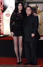 In this Nov. 18, 2010 file photo, Cher, left, and Chaz Bono pose together after a ceremony to put Cher's hands and feet in cement in front of Grauman's Chinese Theatre in Los Angeles. (AP Photo/Matt Sayles, file)