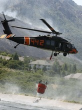 Leah Hogsten  |  The Salt Lake Tribune Three Blackhawk Helicopters traversed the hillsides dousing the fire line with the 600-gal buckets filled with water from two local reservoirs. Firefighters lifted some evacuation orders and called in two hot-shot crews to help battle a still-uncontrolled Utah County wildfire Wednesday. 350 homes remained under mandatory evacuation orders as firefighters fought the nearly 2,900-acre blaze, aided by winds blowing the blaze back up the ridge, away from houses. Wednesday, July 4, 2012 in Alpine