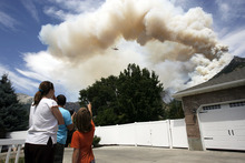 Francisco Kjolseth  |  The Salt Lake Tribune Emily and Byron Smith along with their son Ammon, 9, watch with concern the fire raging behind their house Wednesday, July 4, 2012, after being allowed back into their home following an evacuation the night before.