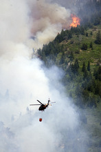 Kim Raff | The Salt Lake Tribune A helicopter works to put out the Quail Wildfire in the hills above Alpine, Utah on July 4, 2012.
