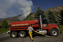 Kim Raff | The Salt Lake Tribune (left) Mike Stevens from Lone Peak Fire fills up a pumper truck with water that will be used to contain the Quail Wildfire that is burning in the hills above Alpine, Utah on July 4, 2012.