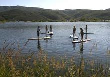 Rick Egan  | The Salt Lake Tribune   Trent Hickman (left) gives a lesson on stand up paddle boarding to the Hale sisters from Ft Lauderdale, Florida, at Jordanelle Reservoir, Thursday, June 14, 2012.