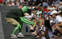 Francisco Kjolseth  |  The Salt Lake Tribune Utah Valley University green man gets high fives from the thousands lining the streets of downtown Provo to watch the Freedom Festival Parade on Wednesday, July 4, 2012.