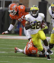 Michigan running back Fitzgerald Toussaint (28) runs with the ball through the Illinois defense during the first half of the NCAA college football game, Saturday, Nov. 12, 2011, in Champaign, Ill. (AP Photo/Seth Perlman)