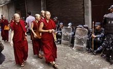 Exile Tibetan nuns arrive at Chusang monastery as Nepalese police officers guard in Katmandu, Nepal, Friday, July 6, 2012. Festivities are held to mark the 77th birthday of the Dalai Lama, who lives in the northern Indian town of Dharmsala after his exile from Tibet during a failed revolt against Chinese rule. (AP Photo/Binod Joshi)