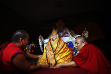 Tibetan monks place a portrait of spiritual leader the Dalai Lama at a monastery in Katmandu, Nepal, Friday, July 6, 2012. Festivities are held to mark the 77th birthday of the Dalai Lama, who lives in the northern Indian town of Dharmsala after his exile from Tibet during a failed revolt against Chinese rule. (AP Photo/Niranjan Shrestha)