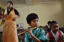 An exile Tibetan child plays flute at a school in New Delhi, India, Friday, July 6, 2012. Festivities are held to mark the 77th birthday of the Dalai Lama, who lives in the northern Indian town of Dharmsala after his exile from Tibet during a failed revolt against Chinese rule. (AP Photo/Tsering Topgyal)