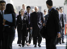 Afghan President Hamid Karzai, center right, walks with U.S. Secretary of State Hillary Rodham Clinton center left, as they arrive for a joint press conference at the Presidential Palace in Kabul, Afghanistan, Saturday, July 7, 2012. Clinton announced that President Barack Obama had designated Afghanistan as a