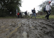 Formula 1 fans walk through mud as they exit a campsite on their way to  Silverstone circuit, England, Saturday, July 7, 2012. Silverstone said they would refund unused tickets for Friday and Saturday and asked anyone with public car parking passes to stay away on Saturday's qualifying day for the race, to ensure fields were not too churned up for Sunday's race after heavy rain caused major disruption.The circuit's managing director Richard Phillips, said Silverstone would not be able to cater for up to 30,000 of the expected crowd of 100,000 on Saturday.  (AP Photo/Lefteris Pitarakis)