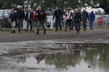Formula 1 fans walk by a puddle at a disused car park on their way to  Silverstone circuit, England, Saturday, July 7, 2012. Silverstone said they would refund unused tickets for Friday and Saturday and asked anyone with public car parking passes to stay away on Saturday's qualifying day for the race, to ensure fields were not too churned up for Sunday's race after heavy rain caused major disruption.The circuit's managing director Richard Phillips, said Silverstone would not be able to cater for up to 30,000 of the expected crowd of 100,000 on Saturday.  (AP Photo/Lefteris Pitarakis)