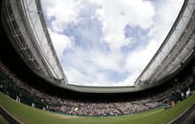 In this photo taken with a fisheye lens, Agnieszka Radwanska of Poland serves to Serena Williams of the United States during the women's final match at the All England Lawn Tennis Championships at Wimbledon, England, Saturday, July 7, 2012. (AP Photo/Alastair Grant)