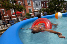 De-Ashia Buchanan, 7, of Washington, leans back in a inflated pool during the seventh annual block party on Newton Street in northwest Washington, during record heat with temperatures in the triple digits, on Saturday, July 7, 2012. (AP Photo/Jacquelyn Martin)