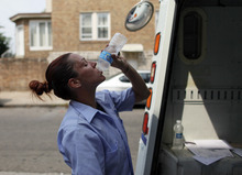 U.S. Postal Service letter carrier Monique Miller drinks from a bottle of water as she delivers mail in the Feltonville section of Philadelphia on Saturday July 7, 2012. Temperatures of more than 100 degrees were forecast in Philadelphia and excessive heat warnings were issued for several states in the Midwest as a heat wave continued. (AP Photo/Joseph Kaczmarek)