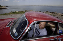 Irv Gordon poses for a picture in his Volvo P1800 in Babylon, N.Y., Monday, July 2, 2012. Gordon's car already holds the world record for the highest recorded milage on a car and he is less than 40,000 miles away from passing three million miles on the Volvo.  (AP Photo/Seth Wenig)
