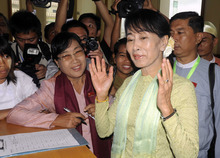 Myanmar opposition leader Aung San Suu Kyi reacts after signing on the registration book to attend a regular session of Parliament at Myanmar's Lower House in Naypyitaw, Myanmar, Monday, July 9, 2012. (AP Photo/Khin Maung Win)