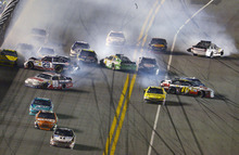 Tony Stewart, front, heads to the finish line for the victory as a multi-car crash takes place behind him during the NASCAR Sprint Cup Series auto race at Daytona International Speedway in Daytona Beach, Fla., Saturday, July 7, 2012. (AP Photo/Phelan M. Ebenhack)