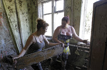 Women remove mud and damaged furniture from their house after flooding in the town of Nizhnebakansky, about 1,200 kilometers (750 miles) south of Moscow, Monday, 9, 2012. Intense flooding in the Black Sea region of southern Russia killed nearly 150 people after torrential rains dropped nearly a foot of water, forcing many to scramble out of their beds for refuge in trees and on roofs, officials said Saturday. (AP Photo/Sergey Ponomarev)