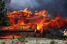 In this Saturday, June 23, 2012 photo provided by Darrell Spangler, a firefighter works the scene of a home being consumed by flames in Estes Park, Colo. As many as 21 structures were destroyed by the fire on Saturday. Eight separate wildfires are burning across Colorado, which is seeing record-breaking heat. (AP Photo/Darrell Spangler) MANDATORY CREDIT