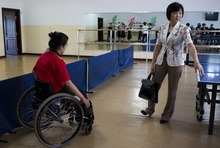 In this June 13, 2012 photo, North Korean Li Pun Hui stands next to a ping pong table as a Paralympic table tennis player passes by in her wheelchair at the Taedonggong Cultural Center for the Disabled in Pyongyang, North Korea.  Putting aside politics, the intensely competitive Li paired up with her arch rival, South Korean star Hyun Jung-hwa, in 1991 as part of the first