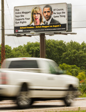 In this July 12, 2012, photo, a pickup truck drives by a National Rifle Association billboard in Hendersonville, Tenn., attacking Tennessee House Republican Caucus chairwoman Debra Maggart. The gun rights group has had a falling out with Republican lawmakers in Tennesseeover a bill seeking to guarantee workers the right to store their guns in their cars while at work.  (AP Photo/Erik Schelzig)