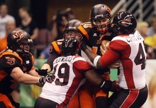 Kim Raff | The Salt Lake Tribune Utah Blaze quarterback Tommy Grady is sacked by Cleveland Gladiators players (left) Tim Cheatwood and Jarrett Crittenton during a game at the EnergySolutions Arena in Salt Lake City, Utah on July 13, 2012.