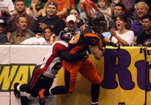 Kim Raff | The Salt Lake Tribune (right) Utah Blaze player Tysson Poots drags Cleveland Gladiators defensive player Dominic Jones down the field after making a catch during a game at the EnergySolutions Arena in Salt Lake City, Utah on July 13, 2012.