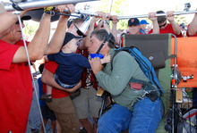 Lawn chair balloonist Kent Couch leans in for a kiss from a grandson before taking flight from his gas station with Iraqi adventurer Fareed Lafta, Saturday, July 14, 2012 in Bend, Ore.. The two men hoped to fly across Oregon, Idaho and into Montana. (AP Photo/Jeff Barnard)