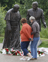 People look at a new statue of former President Ronald Reagan and Pope John Paul II that was unveiled in Gdansk, Poland, on Saturday, July 14, 2012. The statue honors the two men whom many Poles credit with helping to topple communism. (AP Photo/Czarek Sokolowski)