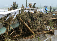 Japan's Ground Self-Defense Force personnel look at trees carried by floodwater following heavy rain in Aso, Kumamoto Prefecture, Japan, Saturday, July 14, 2012. Heavy rain triggered flash floods and mudslides in southern Japan on Thursday, killing nearly two dozens of people. (AP Photo/Kyodo News) JAPAN OUT, MANDATORY CREDIT, NO LICENSING IN JAPAN, CHINA, HONG KONG, SOUTH KOREA AND FRANCE