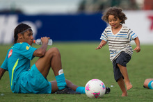 Brazil's Marcelo's son Enzo, right, plays the ball past Brazil's Neymar at the end of a training session in preparation for the London 2012 Olympics in Rio de Janeiro, Brazil, Wednesday July  11, 2012. (AP Photo/Felipe Dana)