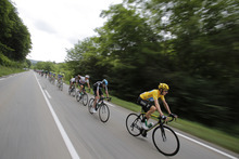 Bradley Wiggins of Britain, wearing the overall leader's yellow jersey, rides in the pack during the 14th stage of the Tour de France cycling race over 191 kilometers (118.7 miles) with start in Limoux and finish in Foix, France, Sunday July 15, 2012. (AP Photo/Christophe Ena)