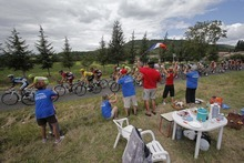 Ccyling fans leave their picnic table to encourage the riders as the pack passes during the 14th stage of the Tour de France cycling race over 191 kilometers (118.7 miles) with start in Limoux and finish in Foix, France, Sunday July 15, 2012. (AP Photo/Christophe Ena)