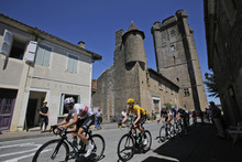 The pack with Bradley Wiggins of Britain, wearing the overall leader's yellow jersey, passes through Bassoues during the 15th stage of the Tour de France cycling race over 158.5 kilometers (98.5 miles) with start in Samatan and finish in Pau, France, Monday July 16, 2012. (AP Photo/Christophe Ena)