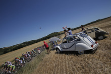 Spectators in classic French Citroen 2CV cars cheer as the pack passes during the 15th stage of the Tour de France cycling race over 158.5 kilometers (98.5 miles) with start in Samatan and finish in Pau, France, Monday July 16, 2012. (AP Photo/Christophe Ena)