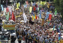Anti-nuclear energy protesters march on a street in Tokyo Monday, July 16, 2012. Tens of thousands of people gathered at a Tokyo park, demanding