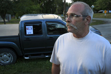 Paul Haarup, the father of the two missing Platte County women, Britny Haarup and Ashley Key, speaks before a candlelight vigil in Edgerton, Mo. on Saturday, July 14, 2012. He has their pictures on flyers taped to the window of his truck, background. The Kansas City Star reported Britny Haarup, 19, and Ashley Key, 22, disappeared Friday from their house in the western Missouri town, leaving Haarup's two young children alone. (AP Photo/The Kansas City Star, Rich Sugg)