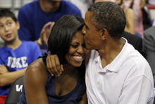 President Barack Obama kisses the head of first lady Michelle Obama, left, after kissing her for